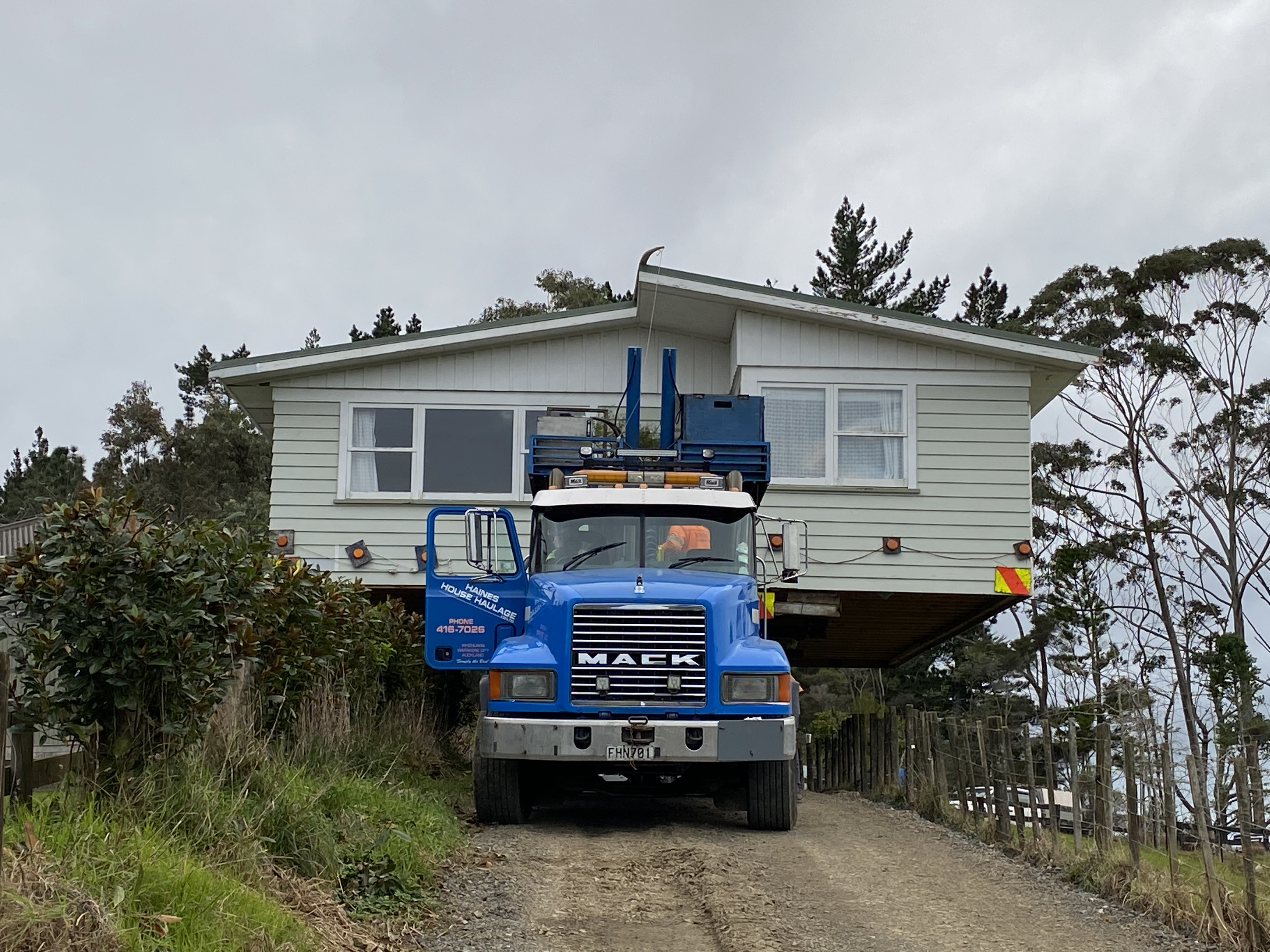 A weatherboard home loaded on the back of a Mack truck getting ready to be moved