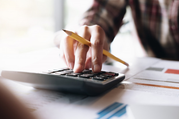 A man with a pencil in his hand using a calculator